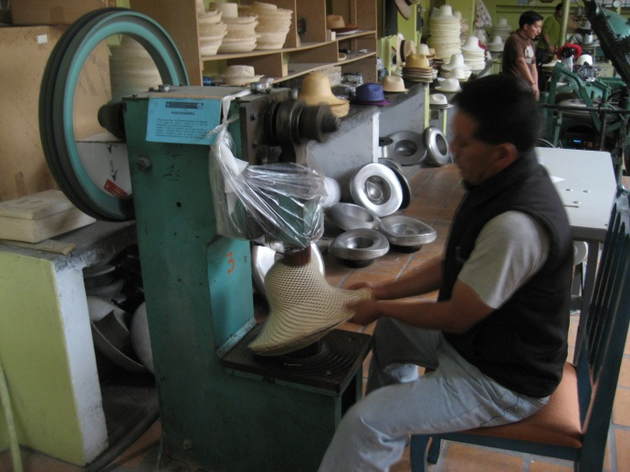 Using a machine that beats a hat into shape and also softens the material