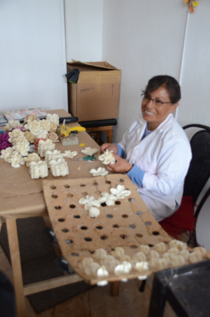 An employee makes flowers out of three pieces of material.  The flowers will be used on some types of hats.
