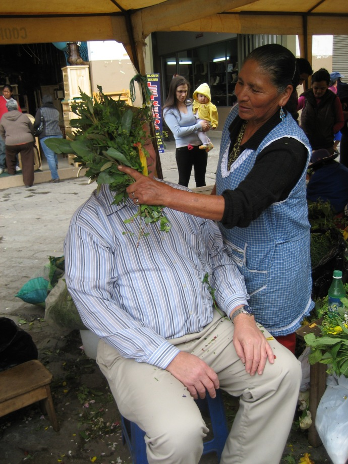 Joe getting smacked by a shaman -- a medicine woman who uses herbal remedies to purge bad spirits.