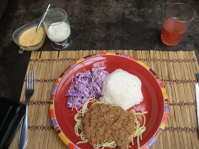 This almuerzo cost $2.50.  Spaghetti with meat sauce, rice, cabbage slaw, traditional juice (usually a watermelon base) and rice pudding are shown.  Also included was a large bowl of spinach and bean soup that was delicious.