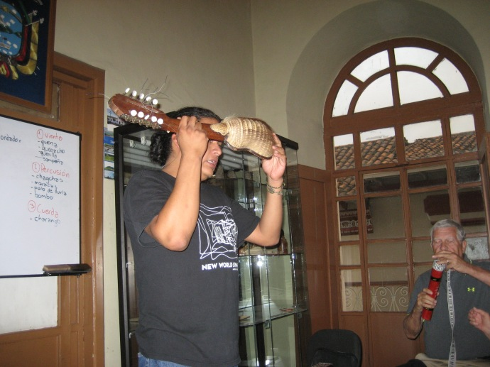 Carlos holds a kirkinchu, a charango made from a real armadillo shell.