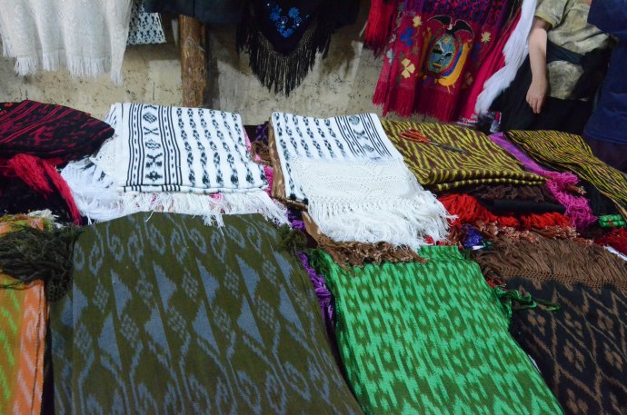 Shawls and scarfs for sale at Tecnica Ikat Macana, most with a price of about $25 - $30USD