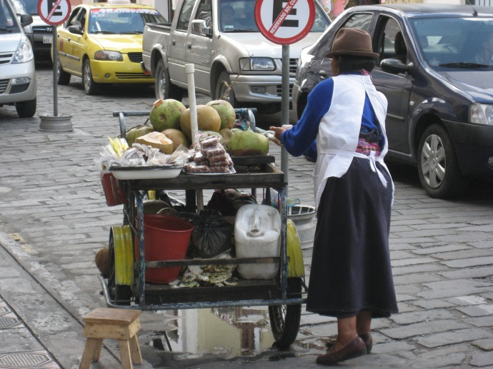 A vendor in native costume sells fruit slices from her pushcart on a downtown street