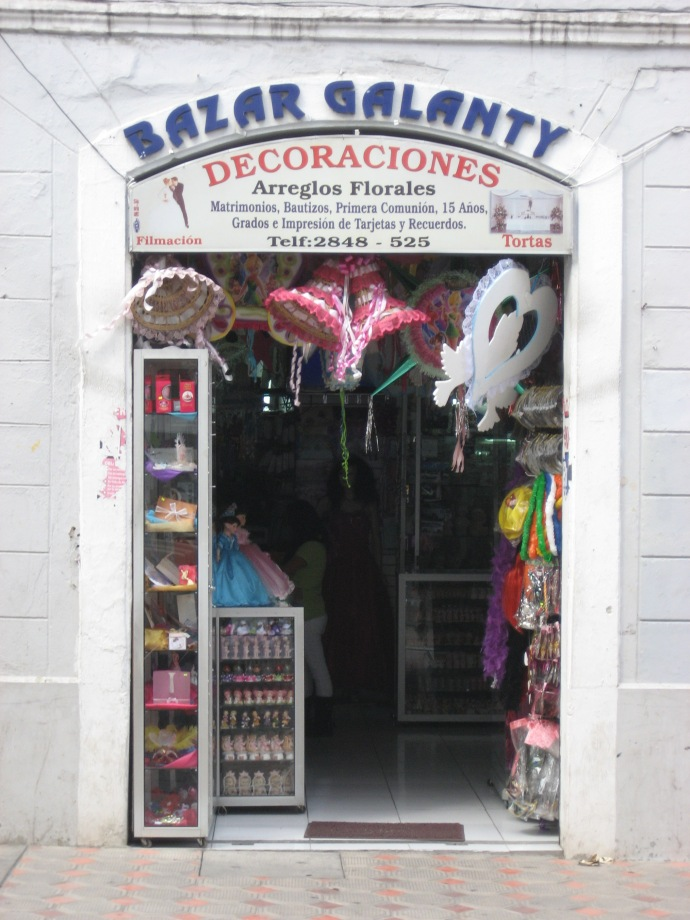 The store front of a party decorations store.  Many of the stores downtown are this size
