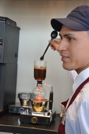 Abel has just added ground coffee to the top of the siphon coffee maker and is stirring the mixture.